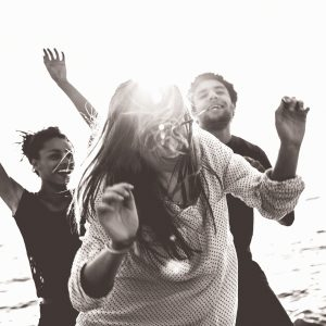 Group of multi-ethnic friends dancing on the beach.