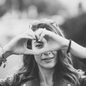 Girlfriend showing heart-shaped symbol with hands to the camera